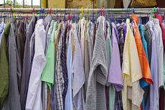 Used shirts hanging at clothes rails Stock Photos