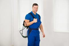 Portrait of confident male worker carrying pesticide container at home Stock Photos