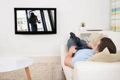 Full length of mid adult man watching movie on television in living room Kuvituskuvat