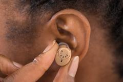 Close-up Of Female Hand Putting Hearing Aid In Ear - stock photo