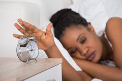 Young African Woman Turning Off Alarm While Sleeping On Bed Stock Photos
