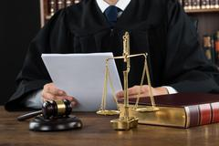 Midsection of judge reading documents at desk in courtroom - stock photo