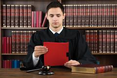 Young male judge reading legal document at desk in courtroom Kuvituskuvat