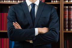 Stock Photo of Midsection of male lawyer standing against bookshelf in courtroom