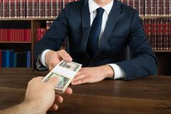 Midsection of lawyer taking bribe from client at desk in courtroom - stock photo