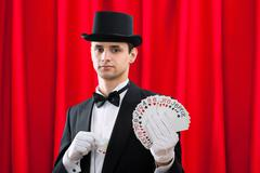 Portrait of young male magician holding fanned out cards against red curtain - stock photo