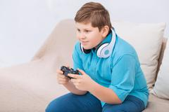 Chubby kid is playing video games Stock Photos