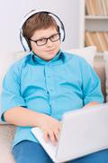 Chubby kid playing games on the laptop - stock photo