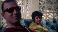 1969: Women smiling on outdoor patio couch with sexy man. TAMPA, FLORIDA Stock Footage