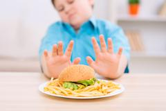 Chubby kid refuses to eat unhealthy food Stock Photos