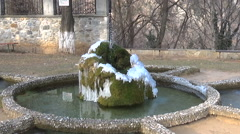 Slow motion zoom in of frozen fountain with ice, snow and moss Stock Footage