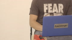 Left to Right Pan of Man on Laptop Labeled Anonymous Stock Footage