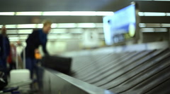Woman collects large suitcase from baggage luggage claim, Lisbon, Portugal Stock Footage
