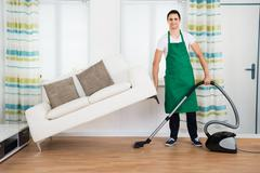Full length of man lifting couch while cleaning hardwood floor with vacuum cl Stock Photos