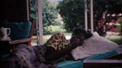 1969: African American girl itching her nose white laying down. CARMEL, INDIANA Stock Footage
