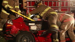 Firefighters lifting teen girl on backboard from car accident Stock Footage