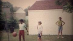 1969: Girl accidentally kicks basketball into sister's face. CARMEL, INDIANA Stock Footage