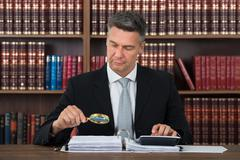 Mature male accountant scrutinizing financial documents at table in office Stock Photos