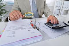 Midsection of male accountant using calculator while holding magnifying glass Stock Photos