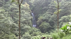 Large waterfall falling in distance between two jungle mountains (HD) Stock Footage