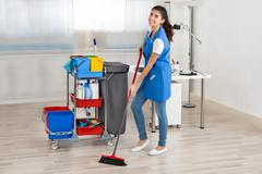 Full length portrait of happy female janitor cleaning floor with broom in off - stock photo