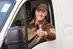 Stock Photo of Portrait of confident delivery man gesturing thumbs up in truck