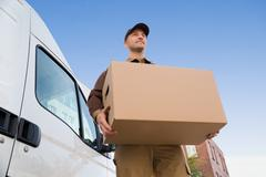 Stock Photo of Low angle portrait of young delivery man carrying cardboard box by truck agai