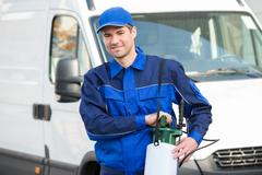 Portrait of confident pest control worker with pesticide against truck Stock Photos