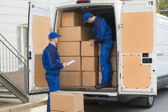 Delivery man unloading cardboard boxes from truck while colleague writing on  - stock photo