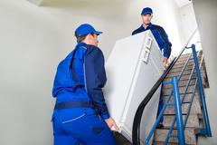 Side view of movers carrying refrigerator while climbing steps at home Stock Photos