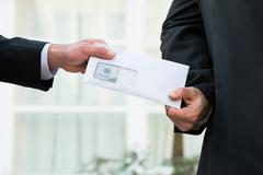 Cropped image of businessman receiving bribe from partner outdoors - stock photo