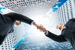 Directly below shot of businessmen shaking hands against office buildings - stock photo