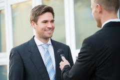 Rear view of male journalist taking interview of happy businessman outdoors - stock photo