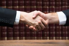 Cropped image of judge and client shaking hands against books at courtroom Stock Photos
