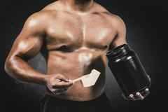 Composite image of muscular man with protein powder Stock Photos