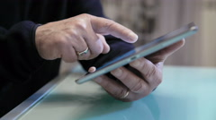 Detail of hands using a tablet, arms leaned on a table Stock Footage