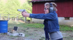 Young girl hesitates to fire a pistol Stock Footage