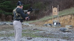 Man in tactical gear loading, priming and unjamming an AR-15 target - stock footage