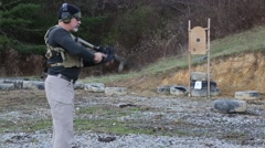 Man in tactical gear loading and firing an AR-15 rifle at a target Stock Footage