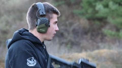 Young man aiming and firing an AR-15 rifle Stock Footage