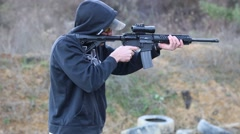 Young man with a hood firing an AR-15 rifle Stock Footage