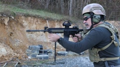 Man with military vest and helmet firing an AR-15 rifle at a gun range Stock Footage