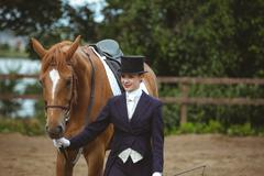 Female jockey leading her horse - stock photo