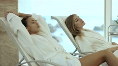 Women in bathrobes lying on the loungers Stock Footage
