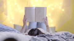Teen Girl Cuddles Up, In Bed, With A Good Book Stock Footage