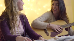 Teen Practices Playing Her Guitar, Her Friend Plays Air Guitar As A Joke - stock footage