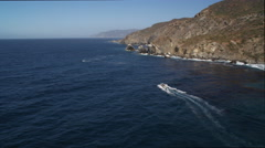 Over a small boat and between sea stacks on Catalina's rugged coast. Shot in Stock Footage