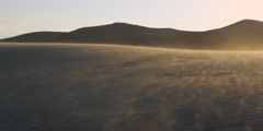 Afternoon light on sand blowing across desert dunes - stock footage