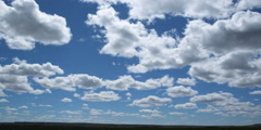 Time-lapse white puffy clouds drifting across blue sky Stock Footage