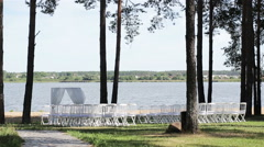 Outdoor wedding decoration. Rows of chairs by lake ready for open air wedding Stock Footage